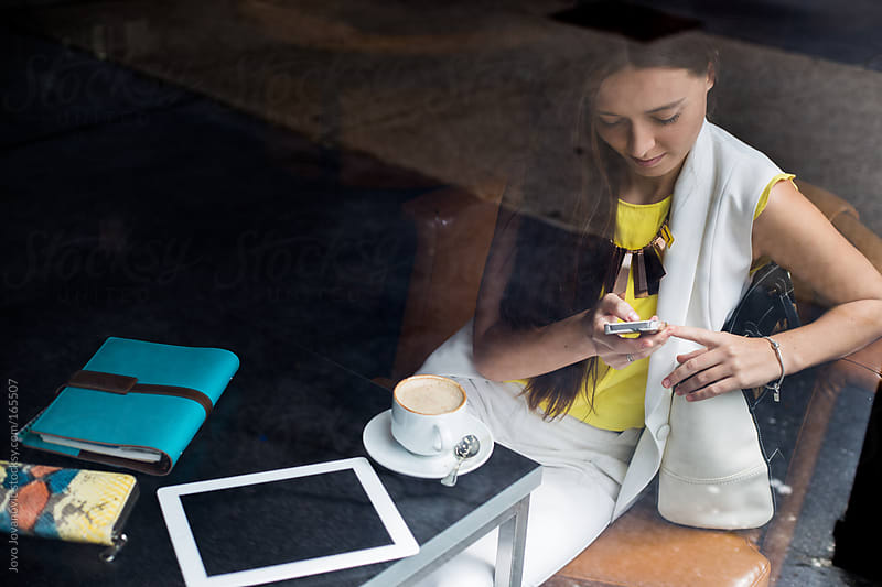 Business woman sitting in coffee shop and checking her phone by Jovo Jovanovic for Stocksy United