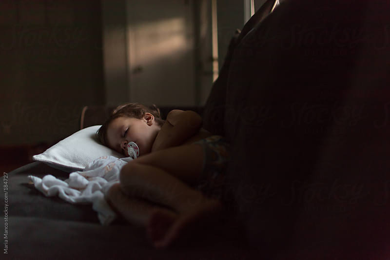 child sleeps on couch by Maria Manco for Stocksy United