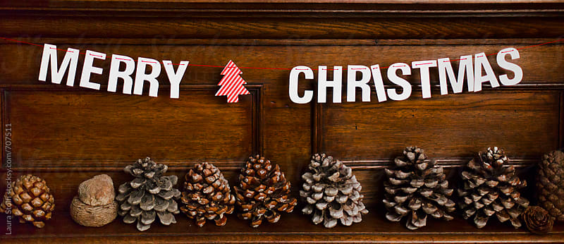 Paper garland saying Merry Cjristmas and pine cones on fireplace top by Laura Stolfi for Stocksy United