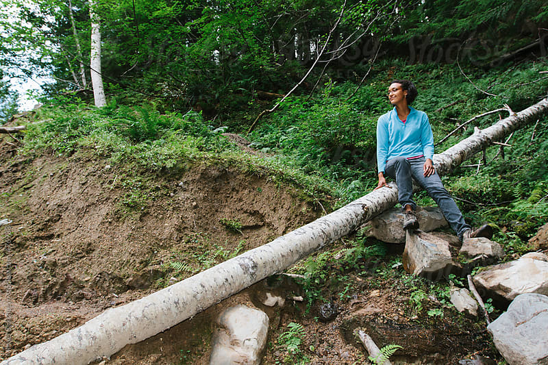 Young African-American woman in a bright shirt sitting on a downed tree in a forest by Mihael Blikshteyn for Stocksy United
