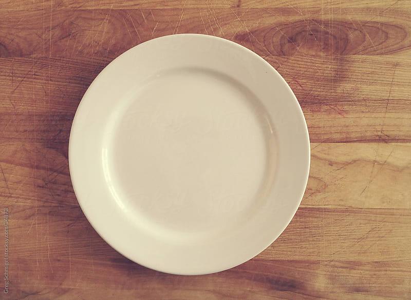 Dinner plate on a wooden board by Greg Schmigel for Stocksy United