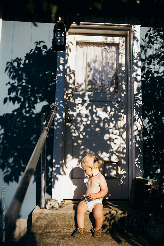 Toddler Boy Sits in the Shadow of a Tree on Back Steps by Amanda Voelker for Stocksy United