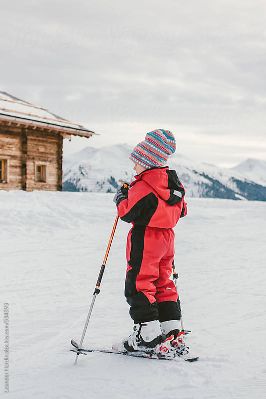 young boy on ski in front of an alpine cabin in snowcovered mountain landscape by Leander Nardin for Stocksy United