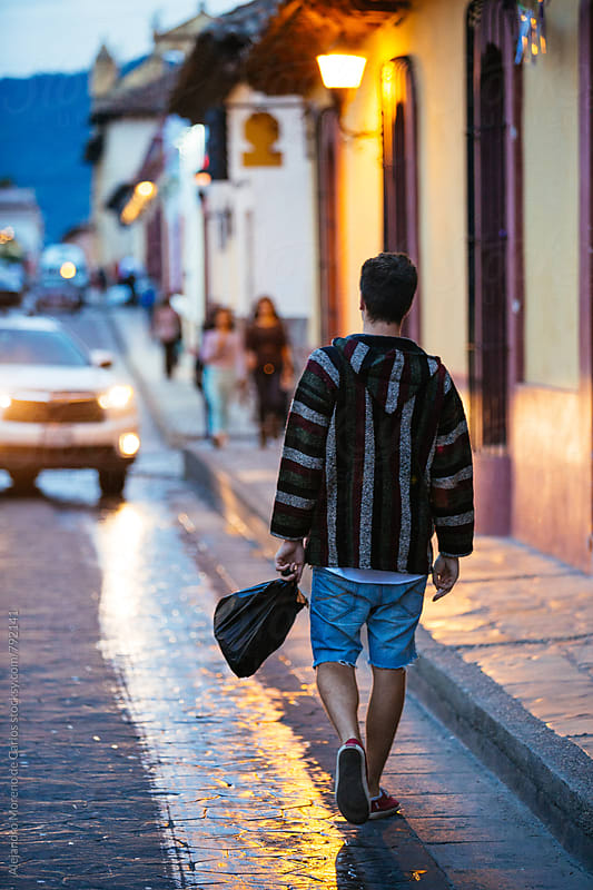Young man walking down the street of a colonial Mexican city at dusk wearing a poncho sweater by Alejandro Moreno de Carlos for Stocksy United