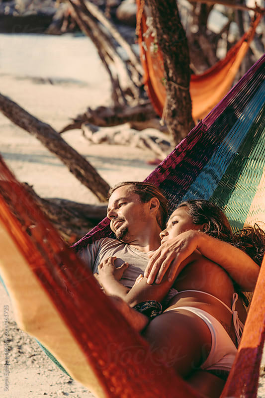 Young mixed couple relaxing in hammock on sandy beach looking at the sea and sunset by Soren Egeberg for Stocksy United