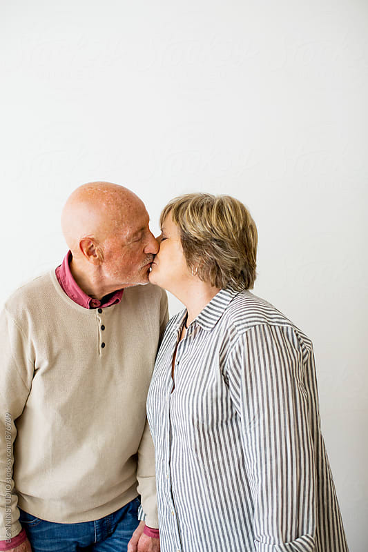 Elderly couple kissing on white. by BONNINSTUDIO for Stocksy United