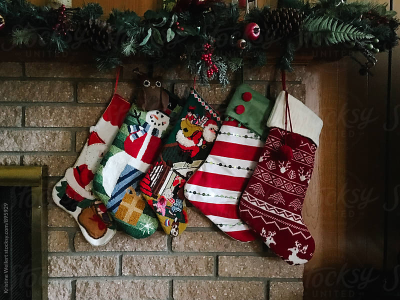 Five stockings hanging from the mantle by Kristine Weilert for Stocksy United