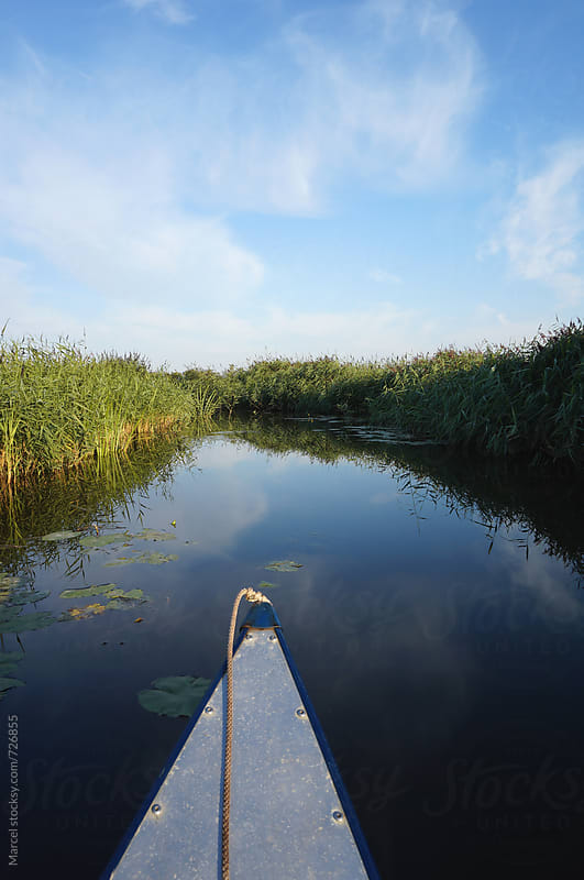 Canoeing on a calm dutch river by Marcel for Stocksy United