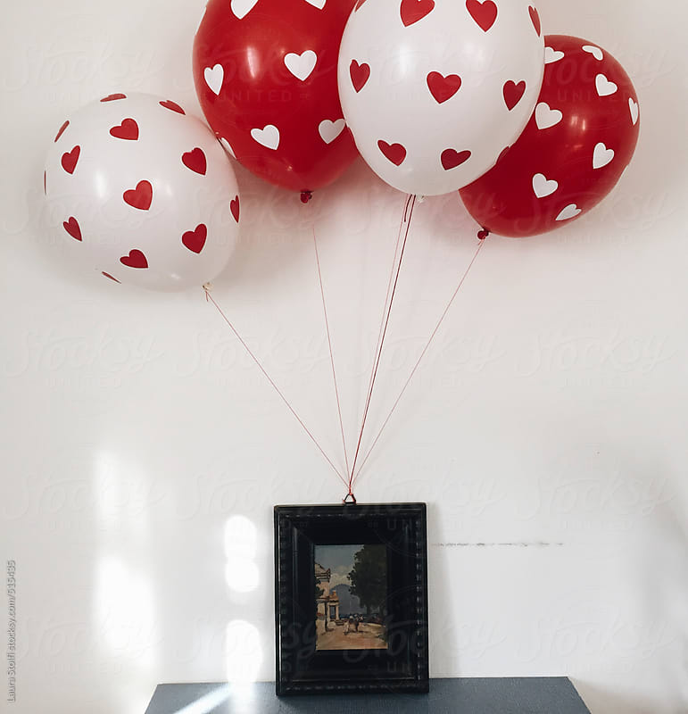 Red and white hearts balloons attached to original painting in wooden frame by Laura Stolfi for Stocksy United