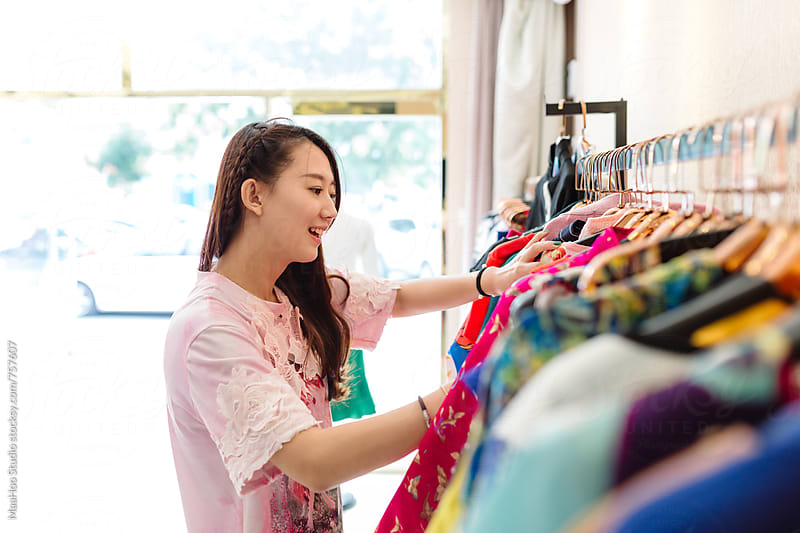 Young woman selecting dresses in clothing store by Maa Hoo for Stocksy United