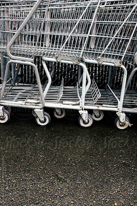 Row of metal grocery carts outside store by Paul Edmondson for Stocksy United