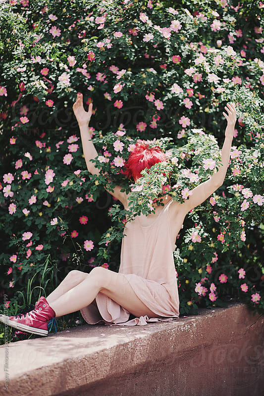 Redhead girl hiding behind a flowering wild rose by Sergey Filimonov for Stocksy United