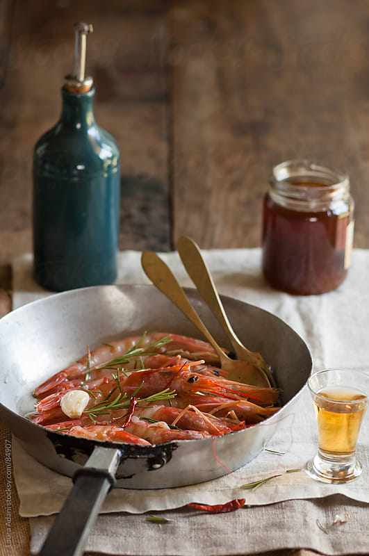 prawns cooked in a pan with honey and rosemary by Laura Adani for Stocksy United