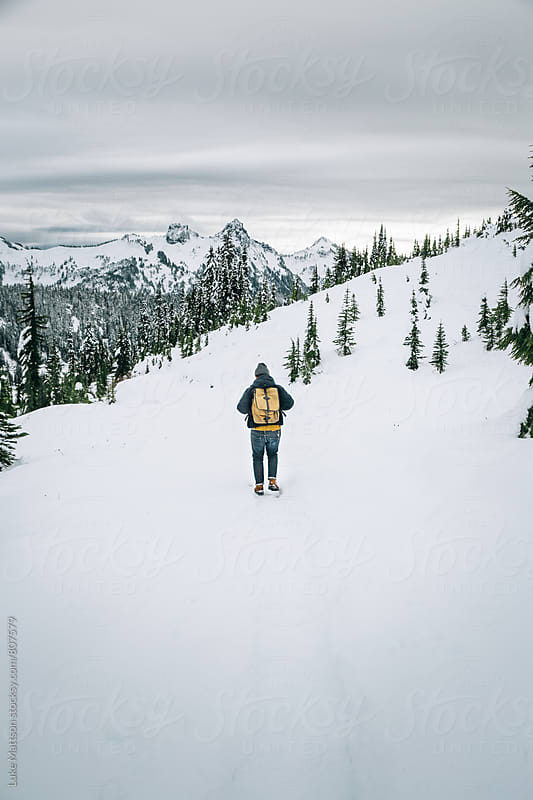 Man Wearing Backpack And Beanie Following Path Through Snowy Mountain Forest by Luke Mattson for Stocksy United