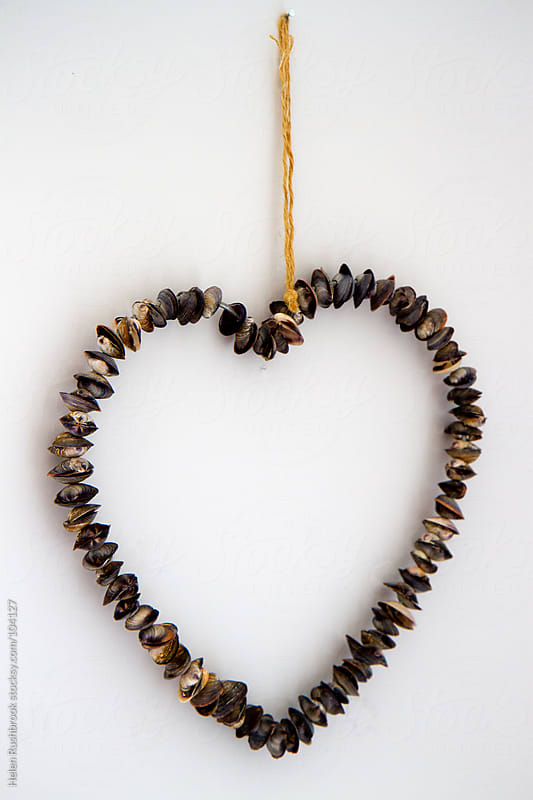 A hanging heart made from seashells by Helen Rushbrook for Stocksy United