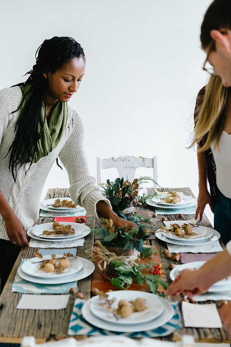 Autumn stock photo of friends setting the table for Thanksgiving dinner by Jen Grantham for Stocksy United