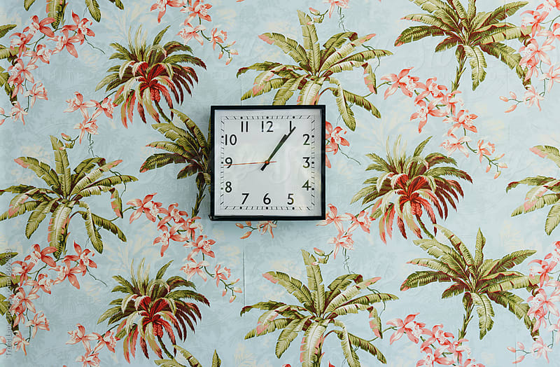 Square clock on wall decorated with beautiful wallpaper by Trent Lanz for Stocksy United