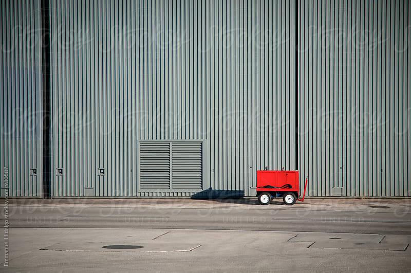 Red airport utility cart abandoned outside building by Emmanuel Hidalgo for Stocksy United