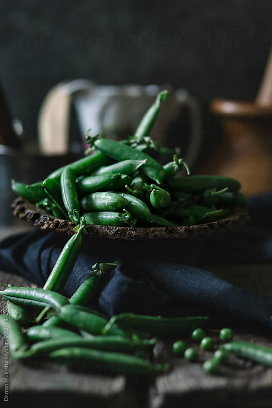 Fresh garden peas in a wooden bowl.  by Darren Muir for Stocksy United