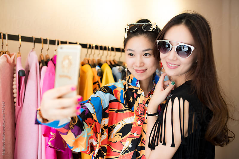 Two young woman taking selfie at clothing store by Maa Hoo for Stocksy United