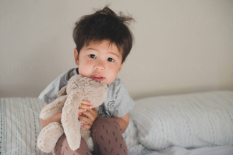 Cute kid hugging stuffed animal by Lauren Naefe for Stocksy United