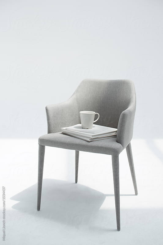 Beautiful chair with books and coffee mug by Miquel Llonch for Stocksy United