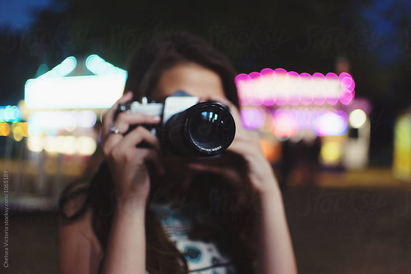 A woman taking a picture at night at a carnival by Chelsea Victoria for Stocksy United