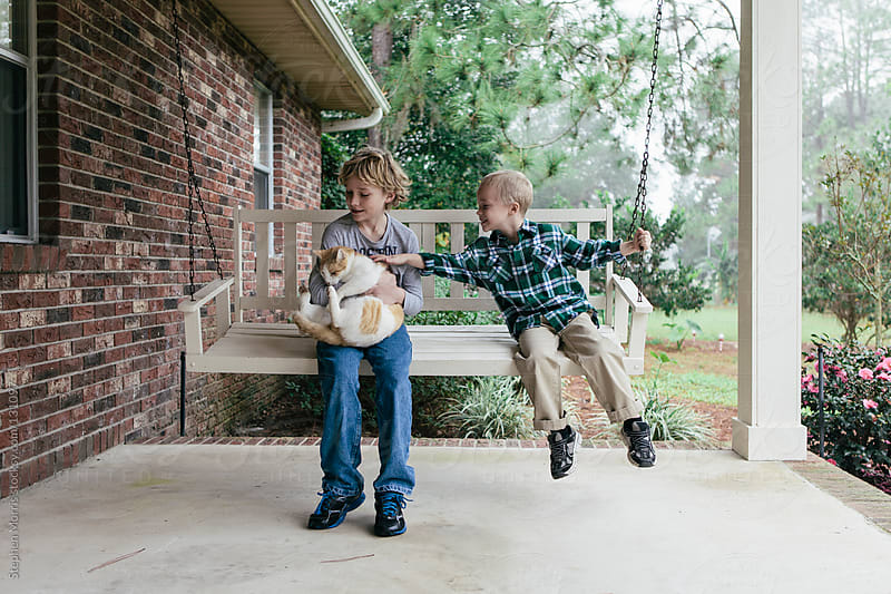 Boys on Porch Swing with Cat by Stephen Morris for Stocksy United