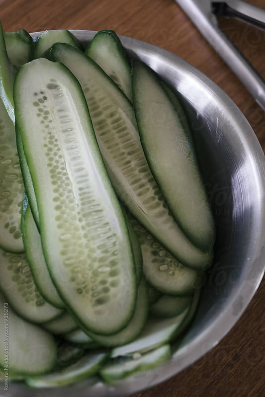 Sliced cucumber for making dill pickle by Rowena Naylor for Stocksy United