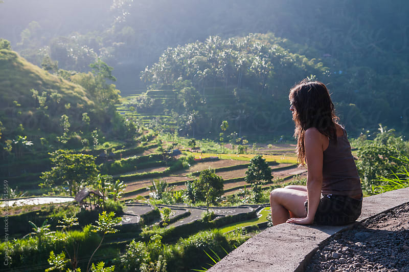 an attractive 20-30 something woman sits overlooking rice paddy field by Caine Delacy for Stocksy United