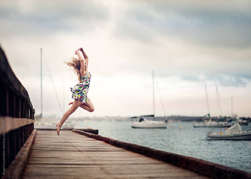 Young girl leaping on a dock above a river on a cloudy day by Angela Lumsden for Stocksy United