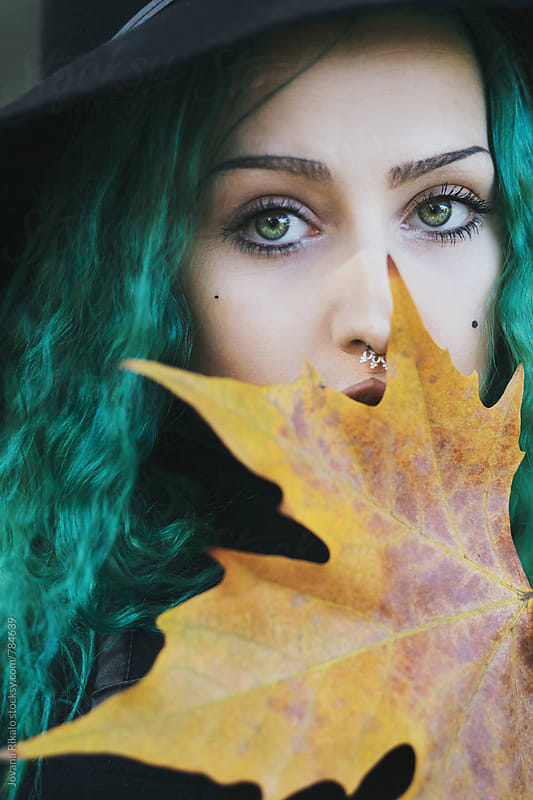 Close up portrait of a young woman holding a leaf by Jovana Rikalo for Stocksy United