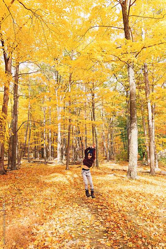 Young boy joyfully jumping in autumn forest by kelli kim for Stocksy United