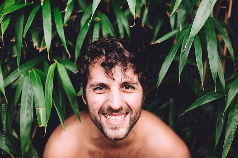 portrait of a man between plants by Thais Ramos Varela for Stocksy United
