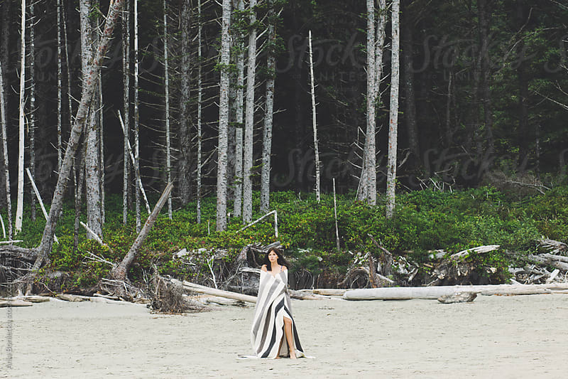 A woman standing on a beach wrapped in a blanket by Ania Boniecka for Stocksy United