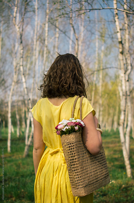 Girl in the yellow dress holding bag with flowers by Aleksandra Jankovic for Stocksy United