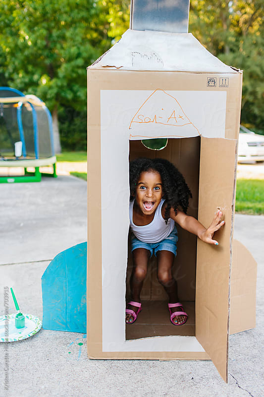 A young child with her cardboard box spaceship by Kristen Curette Hines for Stocksy United