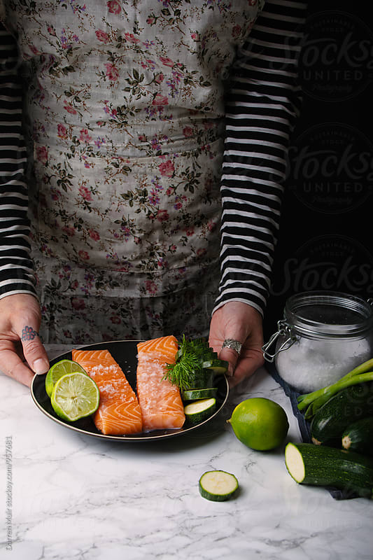 Woman preparing a salmon meal. by Darren Muir for Stocksy United