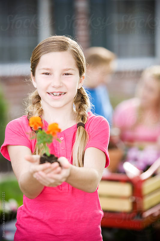 Planting: Cute Girl Holding Out Marigold by Sean Locke for Stocksy United