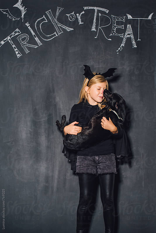 Girl Dressed as a Witch Holding Her Dog by Lumina for Stocksy United