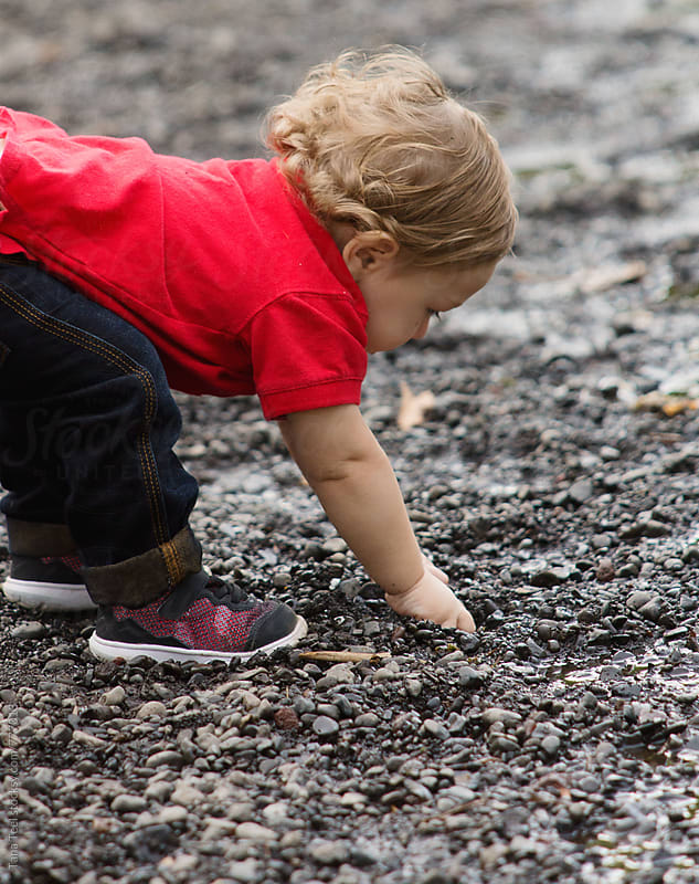 toddler reaches down to get handful of rocks by Tana Teel for Stocksy United