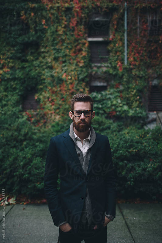 Handsome bearded man surrounded by autumn leaves  by Ania Boniecka for Stocksy United