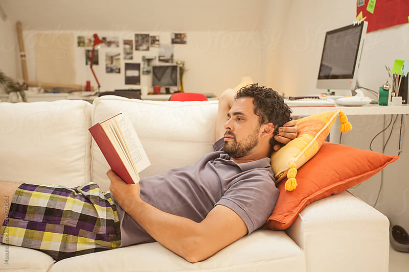 Man Reading a Book on the Sofa by Mosuno for Stocksy United