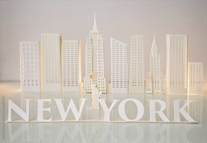 New York written with serif letters with Statue of Liberty in the middle and skyscrapers by Beatrix Boros for Stocksy United