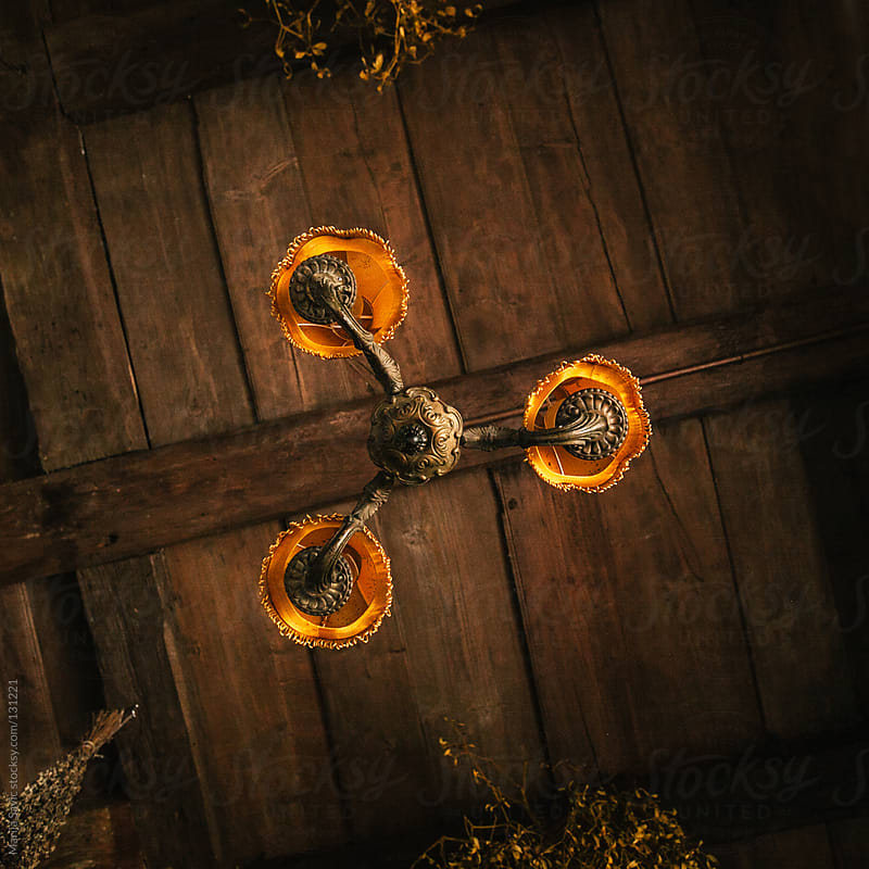Orange chandelier hanging from the wooden ceiling. by Marija Savic for Stocksy United