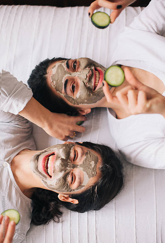 Two beautiful happy female friends with facial masks lying on the bed by VeaVea for Stocksy United