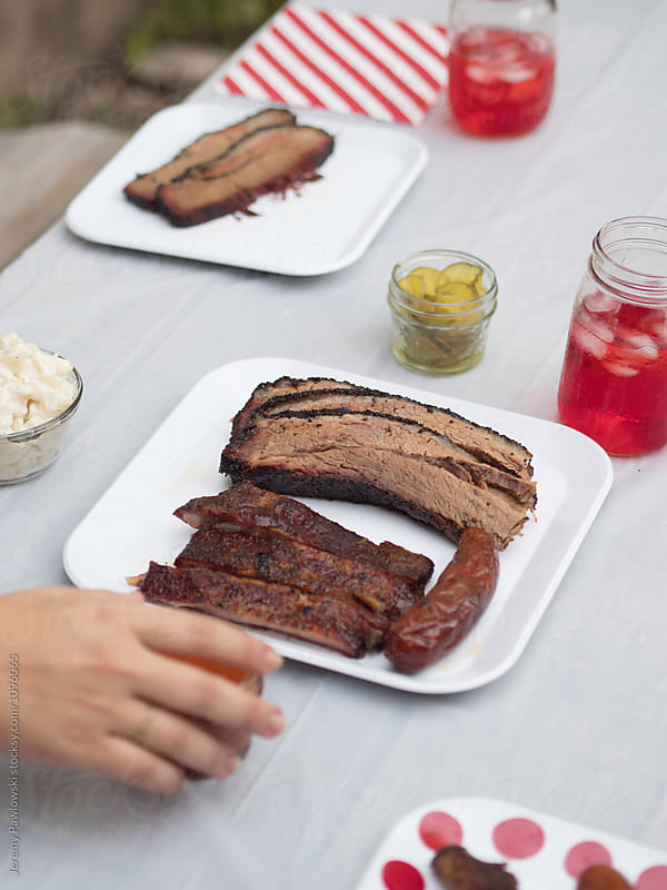 Hand reaching for plate full of brisket, ribs and sausage by Jeremy Pawlowski for Stocksy United