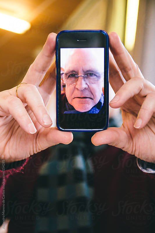 Senior man showing self portrait photo on smartphone by Alejandro Moreno de Carlos for Stocksy United