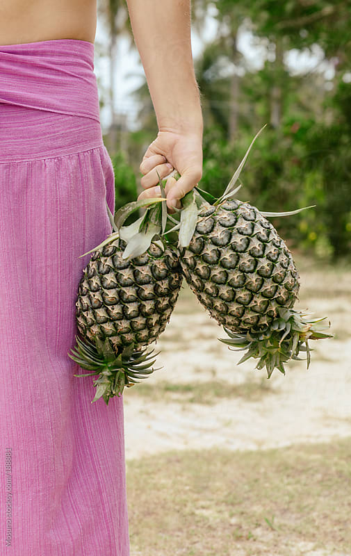 Anonymous Man Holding Pineapples by Mosuno for Stocksy United