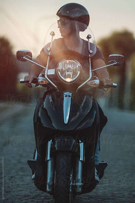 the last rays of the sun,a young man on a motorcycle by Igor Madjinca for Stocksy United